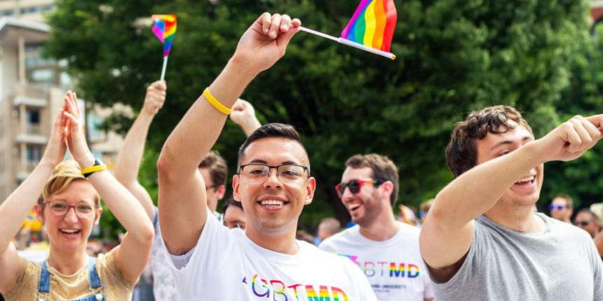 a student waves a rainbow flag at the pride parade in 2019