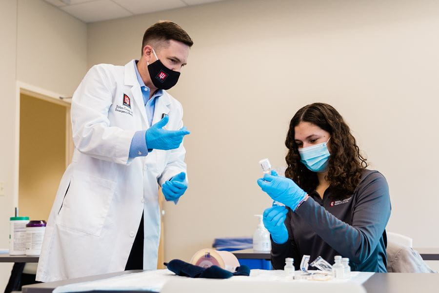 Dylan Cooper, MD, trains a student at the Simulation Center
