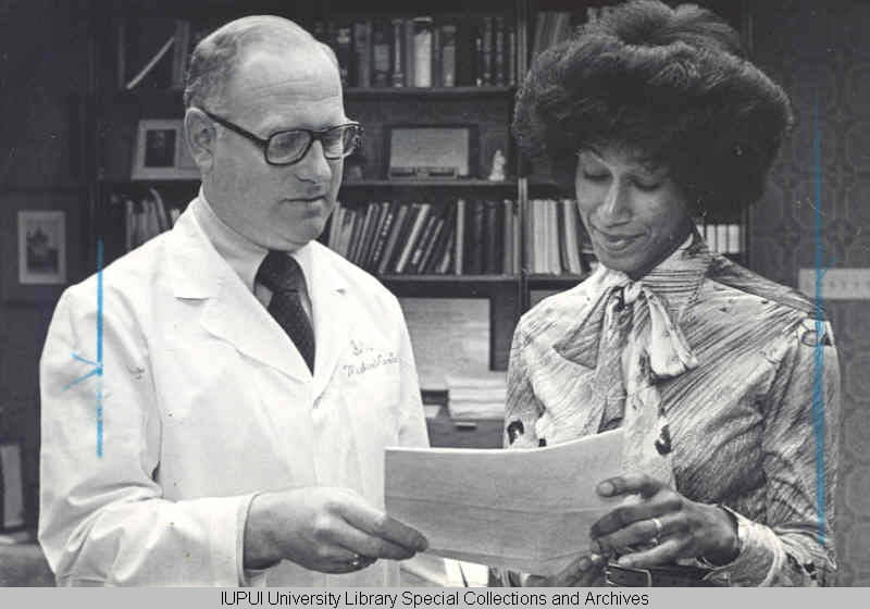 Alicia Monroe, a medical student, accepts the McClean Award from Steven Beering in 1976