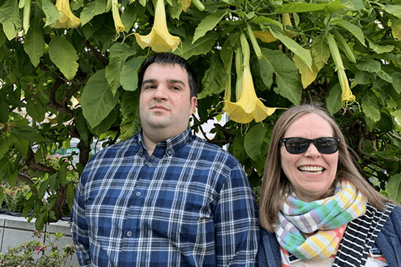 Bob Avera and Mary Wermuth standing in front of an Angel trumpet