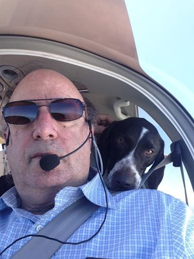 a dog peaks over cary mariash's shoulder as he pilots a plane