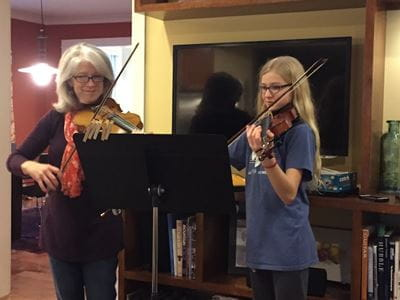Cavaghan and her daughter stand side by side playing the violin together.