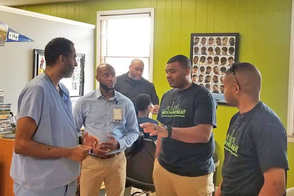 Clark Simons, MD talks with members of Indy HeartBeat at a barbershop