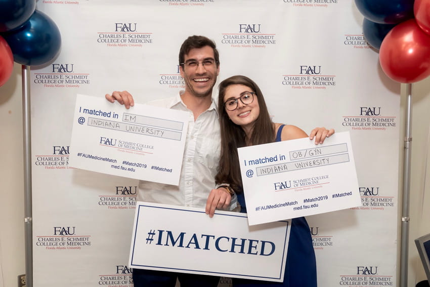 Green and her partner, Ben Krempley, MD, hold signs announcing their couples match