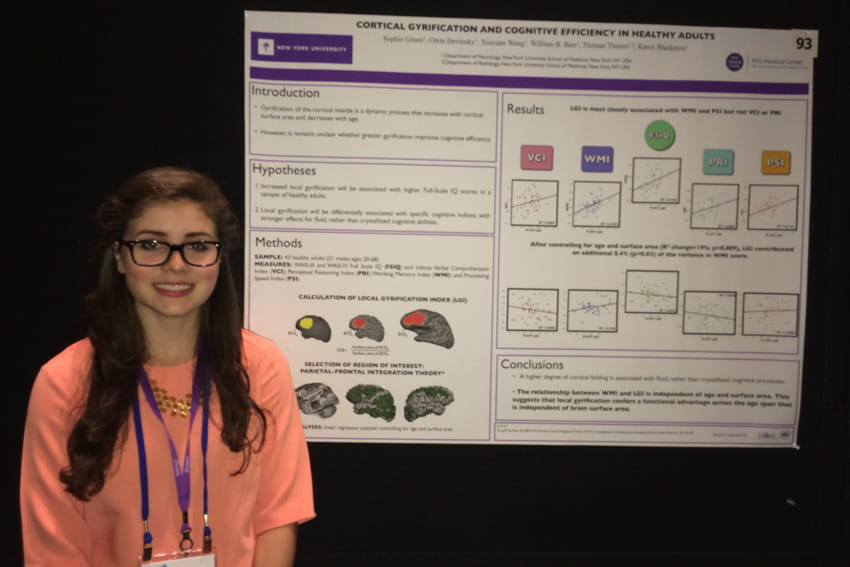 Green poses with a research poster she worked on during college at NYU