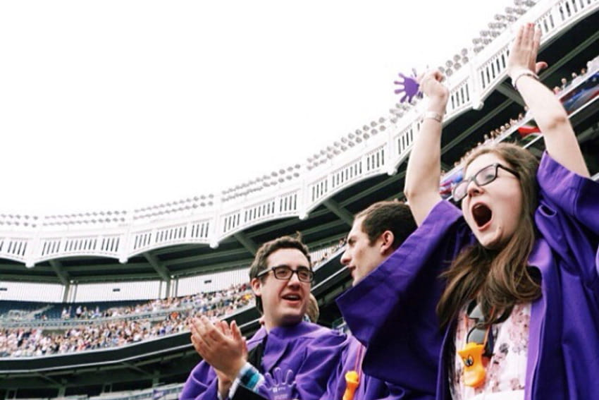 Green celebrates with her hands thrown in the air at NYU graduation