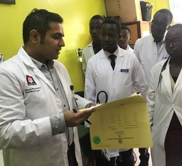 Avinash Mantravadi, MD goes over surgeries with medical students and residents at Moi University School of Medicine.