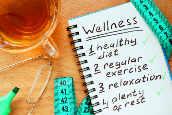 Notebook open with text: Wellness 1) healthy diet; 2) regular exercise; 3) relaxation; 4) plenty of rest