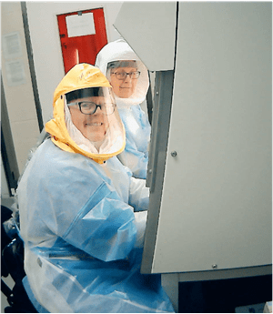 Melissa Kacena and another researcher work while wearing protective coverall suits.