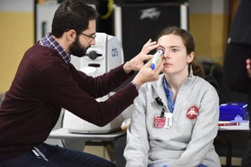 A resident conducts an eye exam on a medical student at the student outreach clinic in Indianapolis.