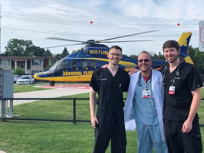 Dr Taylor and colleagues in front of a helicopter