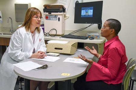 Liana Apostolova listens to a patient from her research study