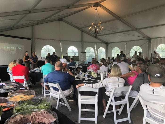 Jamie Renbarger, MD, and Karen Pollok, PhD, sharing research updates with people at the inaugural Tyler Trent golf outing